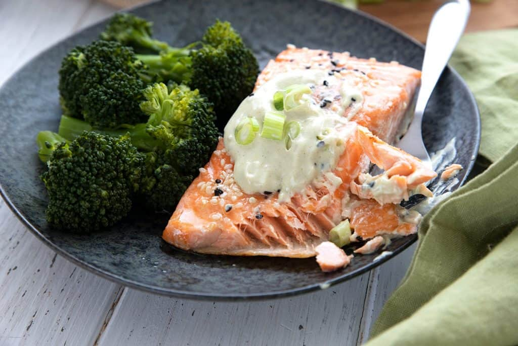 Close up shot of roasted salmon with wasabi mayo, and a forkful taken out of the salmon.