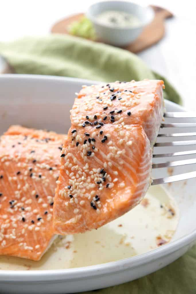 A piece of oven roasted salmon being lifted out of a white baking dish on a spatula.