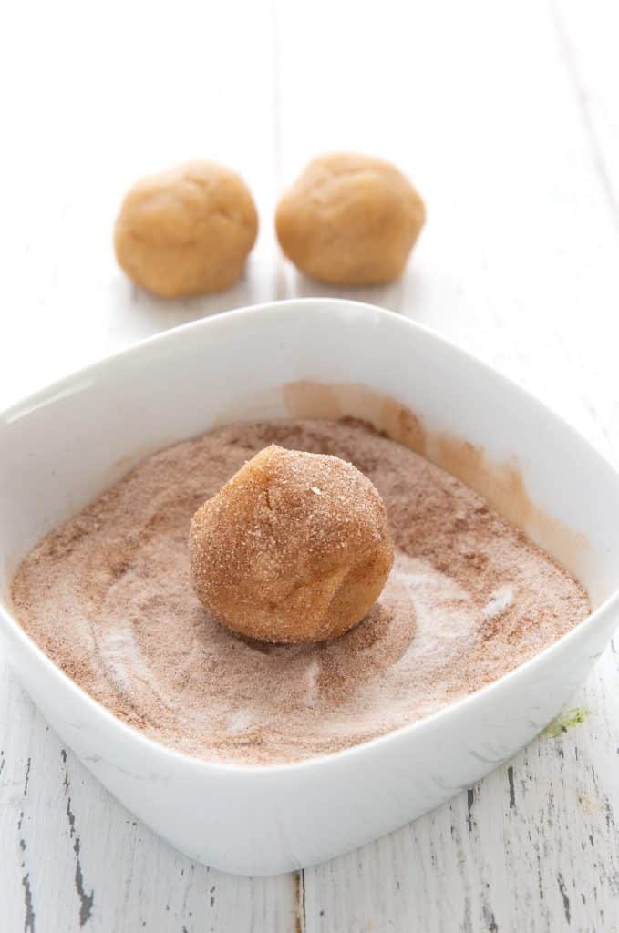 A ball of keto snickerdoodle cookie dough being rolled in a mixture of cinnamon and sweetener.