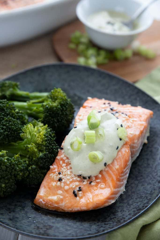 A piece of roasted keto salmon on a black plate with wasabi mayonnaise and chopped green onions on top.