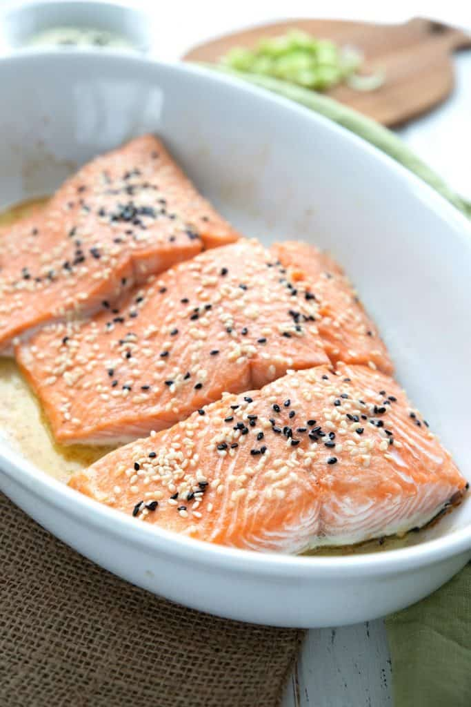 Keto oven roasted salmon in a white dish with sesame seeds on top.